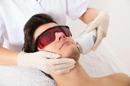 gesicht: Close-up Kosmetikerin, die Haarentfernung mit Laser-Behandlung, um Gesicht des jungen Mannes