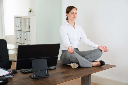 workplace wellness: Young Businesswoman Doing Yoga On Wooden Desk In Office