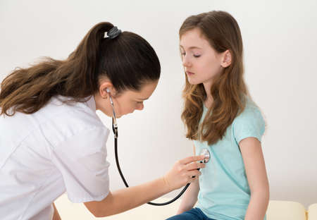 physician: Young Female Doctor Examining Girl With Stethoscope In Hospital