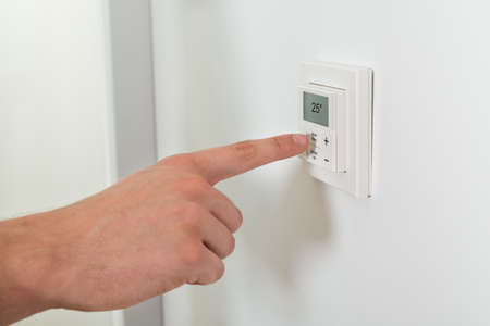 conditioning: Close-up Of Person Hands Adjusting Room Temperature On A Digital Thermostat