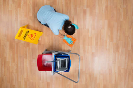 maid service: High Angle View Of Woman Cleaning Floor With Rag