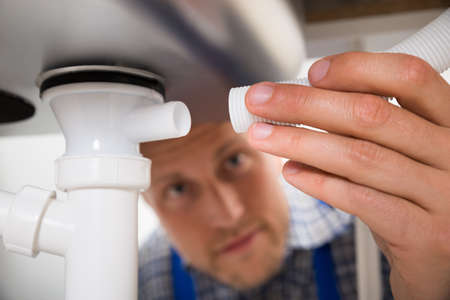 Close-up Of Male Plumber Connecting Pipe To Kitchen Sink Stock Photo