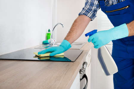 house cleaning: Close-up Of Worker Cleaning Electric Hob At The Countertop With Cloth