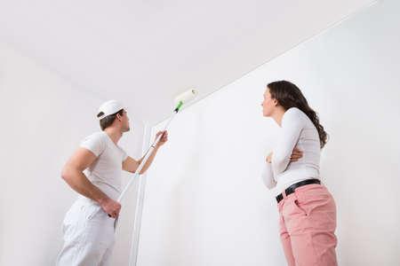 pintor: Mujer joven que mira la Pintor Pintura Blanca En La Pared En Casa Foto de archivo