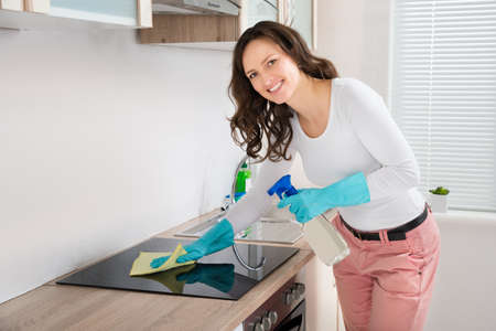 cleaning kitchen: Young Woman Smiling While Cleaning Induction Hob On Countertop At Home Stock Photo