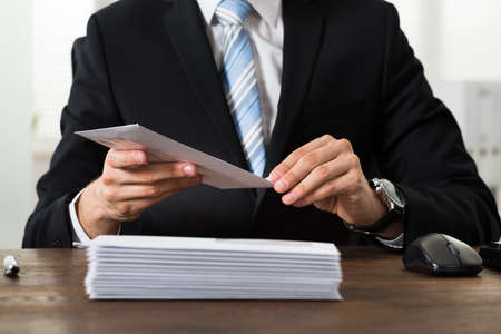 stacks: Close-up Of Businessman With Envelopes At Desk In Workplace