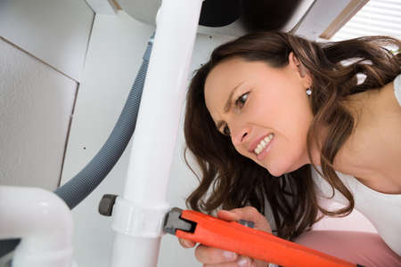 pipe wrench: Close-up Of Woman With Monkey Wrench Tightening White Pipe Stock Photo