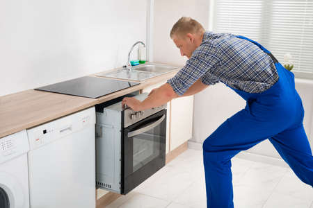 Young Repairman In Overall Repairing Oven In Kitchen