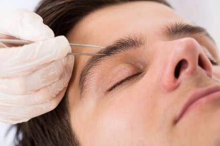 tweezing eyebrow: Close-up Of Beautician Hands Plucking Handsome Man Eyebrows With Tweezers Stock Photo