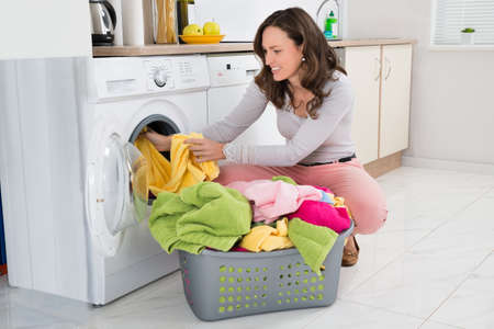 lavadora con ropa: Mujer joven que pone la ropa en lavadora en casa