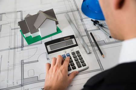 architectural architect: Close-up Of Architect With Blueprint Calculating On Calculator At Desk Stock Photo