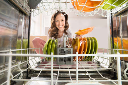 Happy Woman Removing Plate View From Inside The Dishwasher