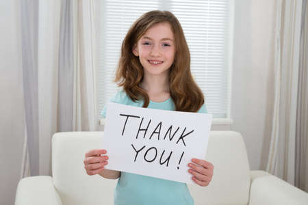 you: Happy Girl Holding Board With The Text Thank You At Home Stock Photo