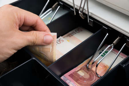 cash box: Close-up Of Person Hands Holding Banknote In Cash Register