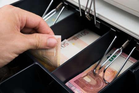 cash money: Primer plano de la persona Manos que sostienen billetes en la caja registradora