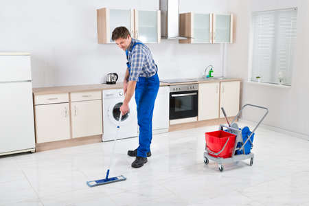 mopping: Young Happy Worker In Overall Mopping Floor Stock Photo
