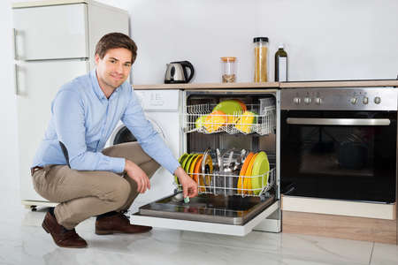 dishwasher: Young Happy Man Putting Dishwasher Soap Tablet In Detergent Dishwasher Box In Kitchen Room Stock Photo