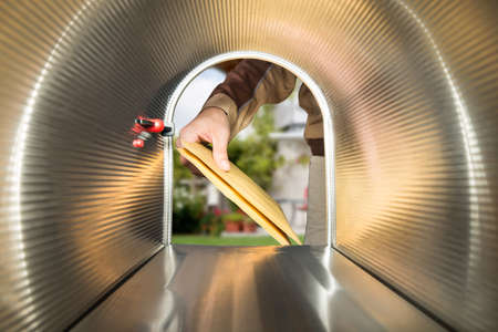 post mail: Close-up Of Postman Hands Putting Letters View From Inside The Mailbox Stock Photo