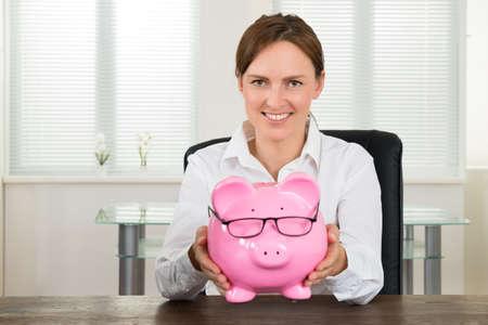 piggybank: Happy Businesswoman Sitting On Chair Holding Pink Piggybank At Desk