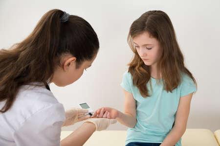 Glucometer と女の子の血糖値計測白衣の医者 写真素材 - 43694234