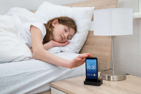 early morning: Girl Lying On Bed Snoozing Mobile Phone Alarm Clock In Bedroom