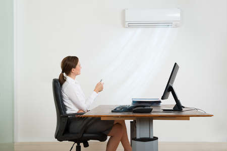 fresh air: Young Businesswoman Sitting On Chair Using Air Conditioner In Office