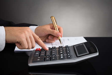 bookkeeping: Close-up Of Businessperson Hands Doing Calculation At Desk