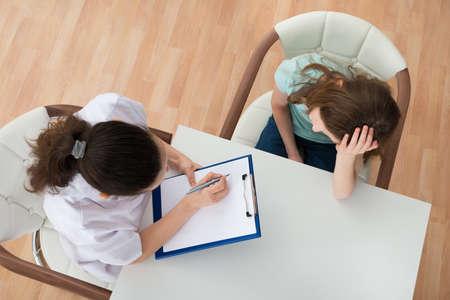 psicologia infantil: Opinión de alto ángulo Doctora reconfortante paciente deprimido se sienta en la tabla