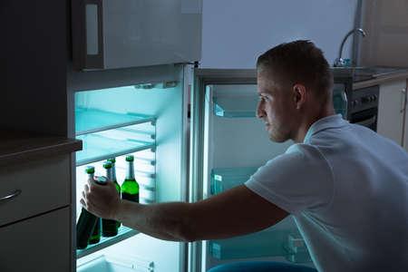 tomando refresco: Hombre joven que quita la botella de cerveza de la nevera en la noche en la cocina de habitaciones