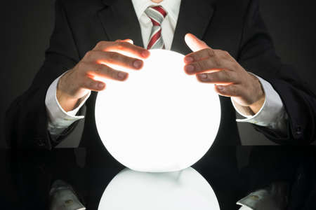 Close-up Of Businessman Predicting Future With Crystal Ball At Desk Stockfoto