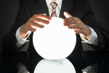 vision futuro: Primer plano del hombre de negocios Predicción de futuro con la bola de cristal en el escritorio