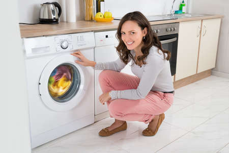 clothes washer: Young Happy Woman Cleaning Multi-colored Clothes In Washing Machine At Home Stock Photo
