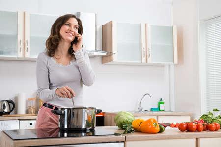 キッチンで料理をしながら携帯電話で話している幸せな女