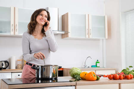 cupboard: Happy Woman Talking On Mobile Phone While Cooking In Kitchen Stock Photo