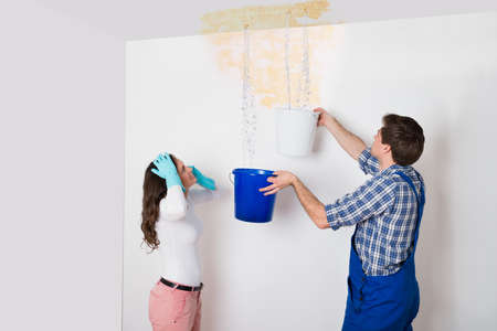 Young Woman Standing With Worker Collecting Water In Bucket From Ceiling In House Stockfoto