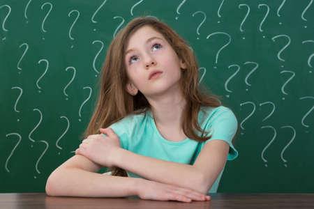 confundido: Contemplando que se sienta en el escritorio con el signo de interrogaci�n dibujado con tiza en la pizarra Foto de archivo