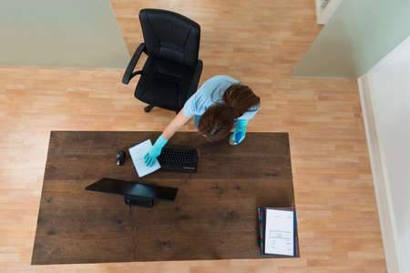 High Angle View Of Young Woman Cleaning Keyboard At Desk In Office