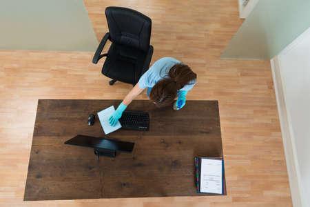 orden y limpieza: Vista elevada de la mujer joven de limpieza del teclado en el escritorio