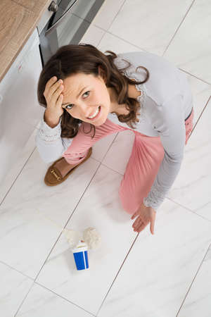 top angle: High Angle View Of Young Woman Looking At Yoghurt Spilled On Floor Stock Photo