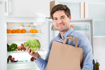 refrigerador: Hombre Feliz Con Bolso de ultramarinos Coloca Cerca El Open Nevera Con Healthy Food Products Foto de archivo