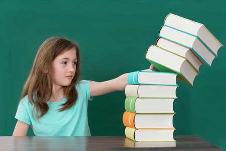 tarea escolar: Estudiante en el escritorio Empujar Pila De Libros Coloridos En Aula