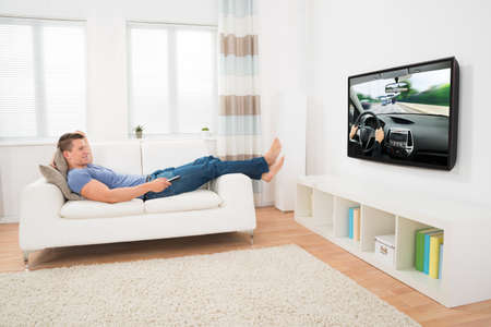 Happy Man Watching Movie While Lying On Sofa At Home