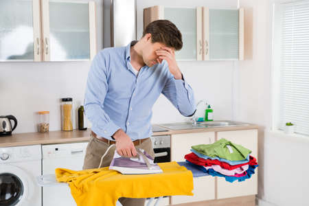 Hot house: Exhausted Young Man Ironing Clothes On Ironing Board Stock Photo