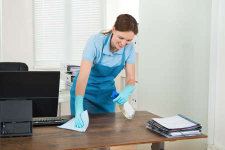 Young Happy Worker Cleaning Desk With Rag In Office