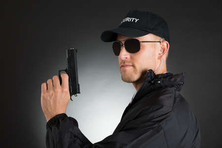 security uniform: Portrait Of Young Bodyguard Holding Gun Over Black Background