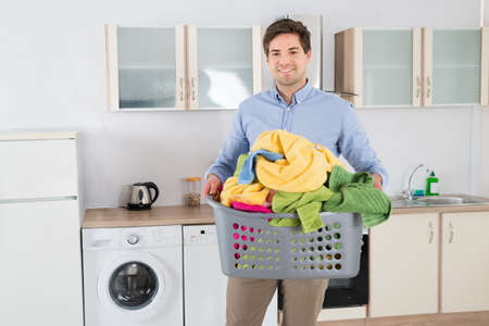 man laundry: Young Handsome Man Carrying Basket With Heap Of Clothes In Kitchen Stock Photo
