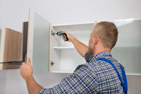 kitchen device: Male Carpenter Drilling In Cabinet With Electric Cordless Drill