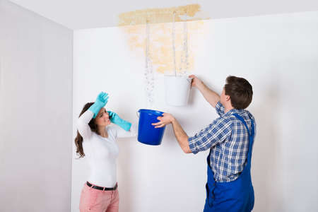 Young Woman Standing With Worker Collecting Water In Bucket From Ceiling In House Stock Photo