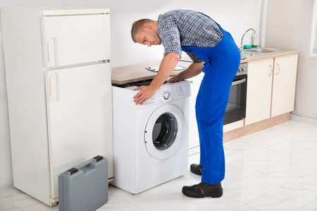 overall: Young Man In Overall Repairing Washing Machine Stock Photo