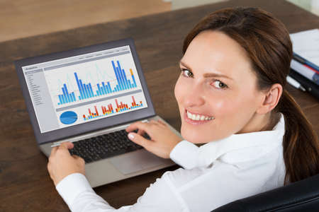 working on laptop: Happy Businesswoman Working With Graphs On Laptop At Desk